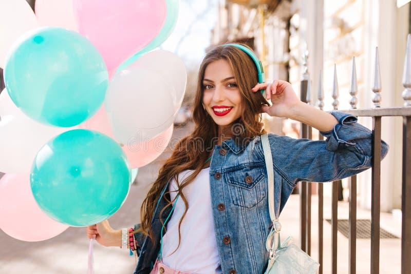 Närbildstående av den ursnygga lockiga flickan i grov bomullstvillomslaget som poserar med födelsedagballonger utanför Förtjusand royaltyfria foton