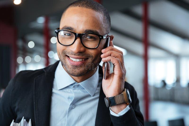 Närbildstående av en affärsman som talar på telefonen royaltyfri foto