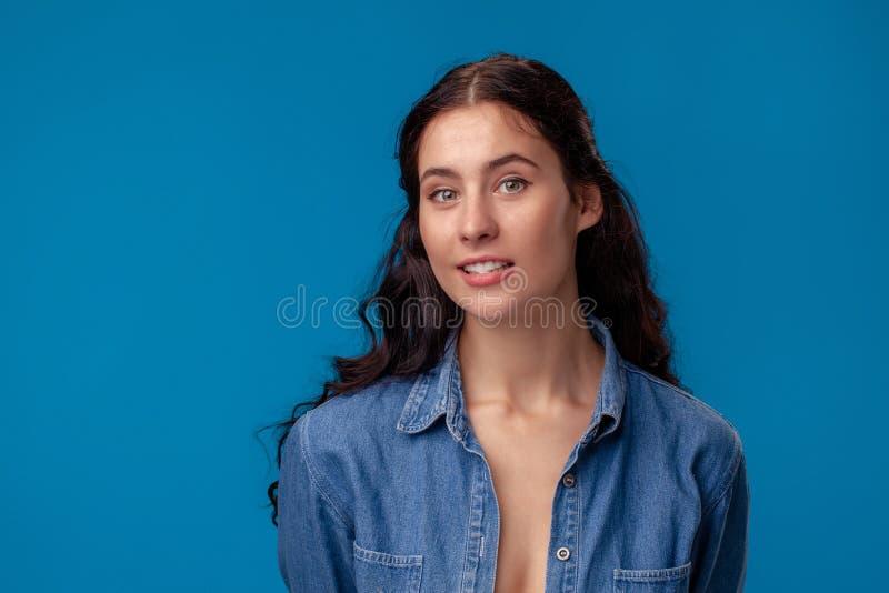 Närbildstående av en attraktiv brunettflicka med långt lockigt hår som poserar på en blå bakgrund royaltyfri foto