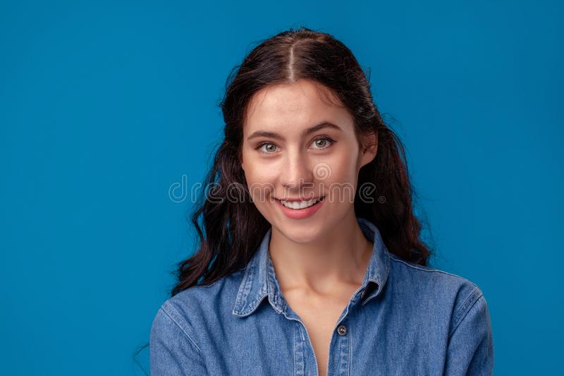 Närbildstående av en attraktiv brunettflicka med långt lockigt hår som poserar på en blå bakgrund arkivfoto