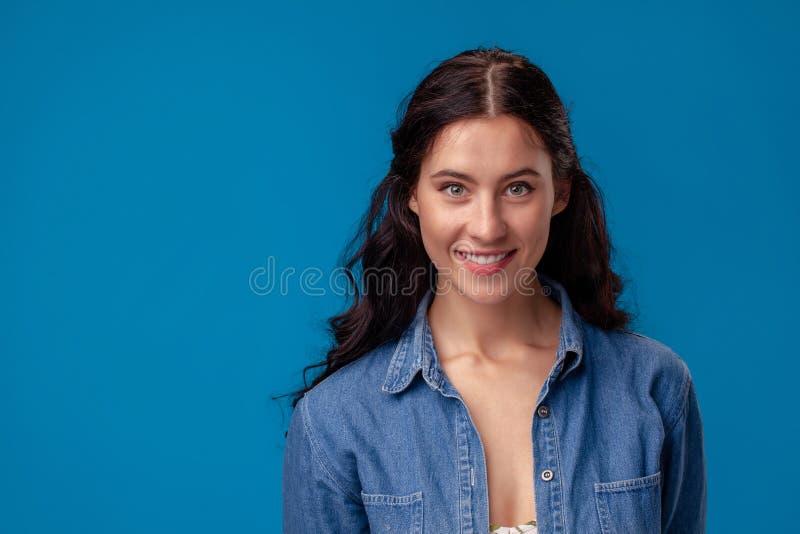 Närbildstående av en attraktiv brunettflicka med långt lockigt hår som poserar på en blå bakgrund royaltyfria bilder