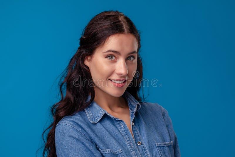Närbildstående av en attraktiv brunettflicka med långt lockigt hår som poserar på en blå bakgrund royaltyfri bild