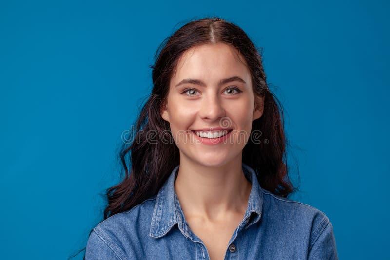 Närbildstående av en attraktiv brunettflicka med långt lockigt hår som poserar på en blå bakgrund arkivfoton