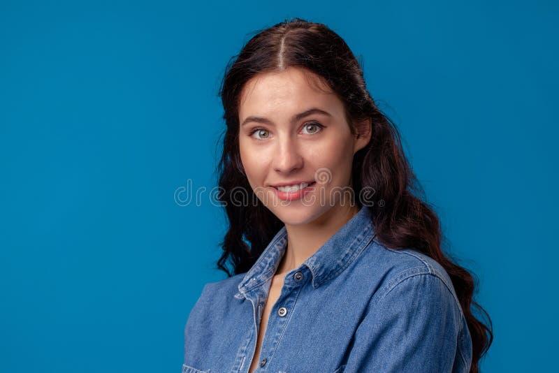 Närbildstående av en attraktiv brunettflicka med långt lockigt hår som poserar på en blå bakgrund royaltyfri fotografi