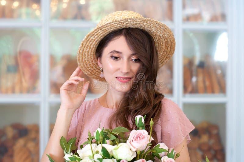 Närbildstående av en attraktiv ung kvinna i en sommarklänning- och sugrörhatt som rymmer en bukett av blommor mot en bakgrund royaltyfri foto