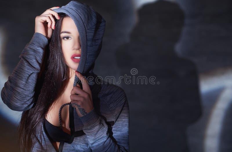 Närbildstående av en förförisk brunettflicka i en hoodie som poserar i studion royaltyfria bilder