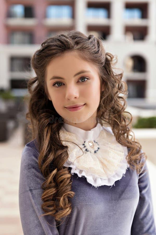 Närbildstående av en flicka i retro klänning och krullning på byggnadsbakgrund fotografering för bildbyråer