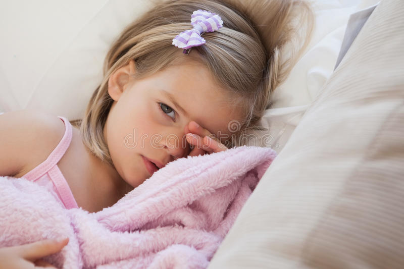 Närbildstående av en gullig flicka som vilar på soffan arkivbilder