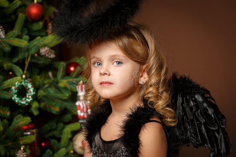 Närbildstående av en gullig liten blond flicka med blåa ögon i en svart demon-demon dräkt mot bakgrunden av jul arkivfoton