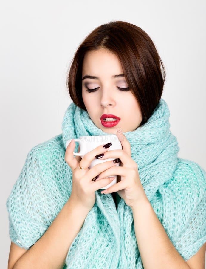 Närbildstående av en härlig kvinna i woolen halsduk och att dricka varmt te eller kaffe från den vita koppen arkivfoton