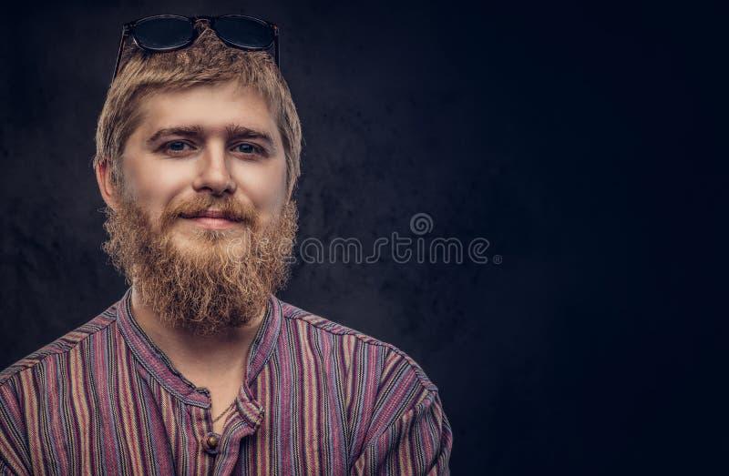 Närbildstående av en le stilig skäggig man i en gammalmodig skjorta på en mörk bakgrund royaltyfri bild