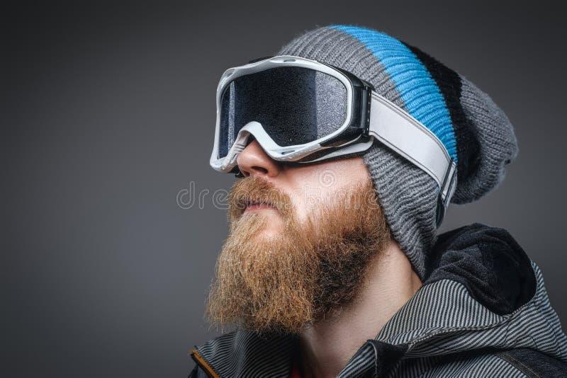 Närbildstående av en man med ett rött skägg som bär en vinterhatt, ett lag och skyddande snöexponeringsglas som bort ser royaltyfri foto