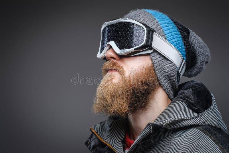 Närbildstående av en man med ett rött skägg som bär en vinterhatt, ett lag och skyddande snöexponeringsglas som bort ser royaltyfri fotografi