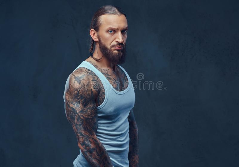 Närbildstående av en muskulös naken skäggig tattoed man med en stilfull frisyr i en sportswear arkivfoto