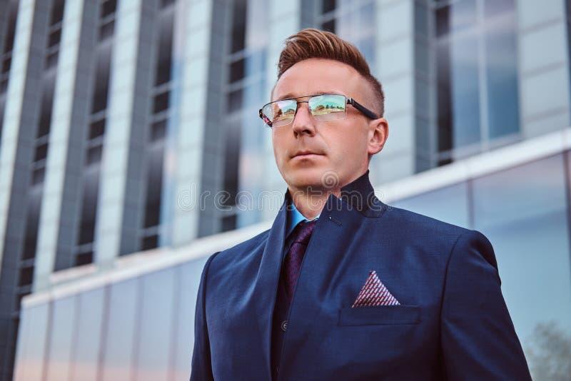 Närbildstående av en säker stilig man i en elegant dräkt och exponeringsglas som ser bort, medan stå utomhus royaltyfri foto