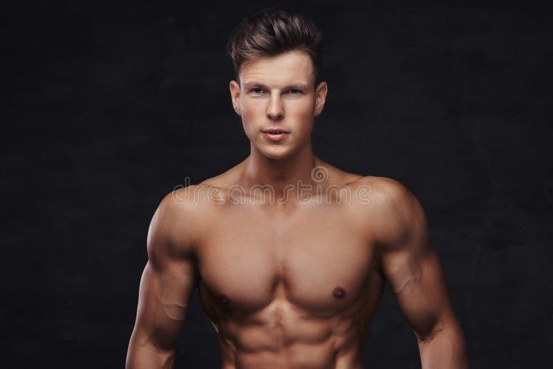 Närbildstående av en sexig shirtless modell för ung man med en muskulös kropp och en stilfull frisyr som poserar på en studio fotografering för bildbyråer