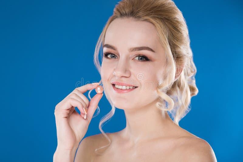 Närbildstående av en ung flicka på en blå bakgrund royaltyfri foto