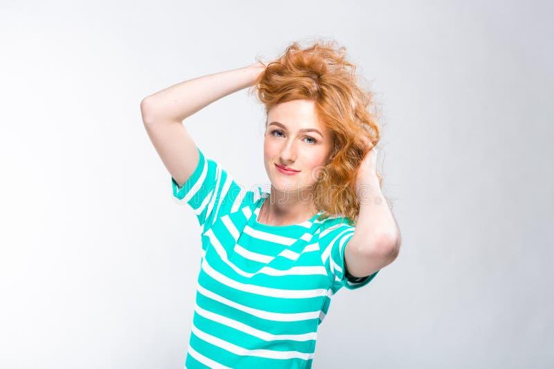Närbildstående av en ung härlig kvinna med rött lockigt hår i en sommarklänning med remsor av blått i studion på gråa lodisar arkivbild
