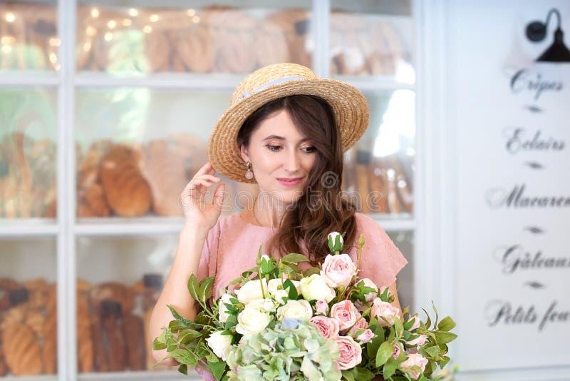 Närbildstående av en ung härlig lycklig dam som bär en stilfull klänning och hatt som promenerar gatan av en europeisk stadsintel royaltyfria foton