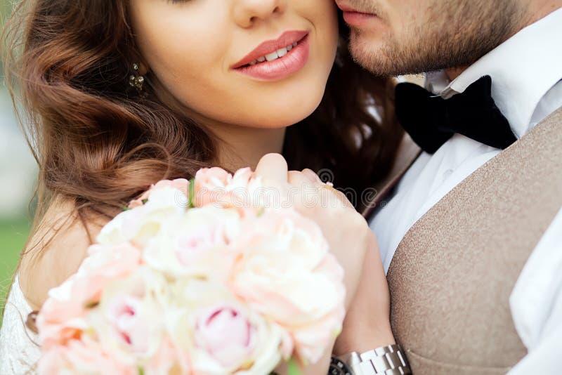 Närbildstående av ett brud- och brudgumanseende på stadsgatan och älskvärt krama fotografering för bildbyråer