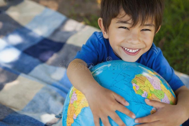 Närbildstående av ett hållande jordklot för gullig pojke arkivbild