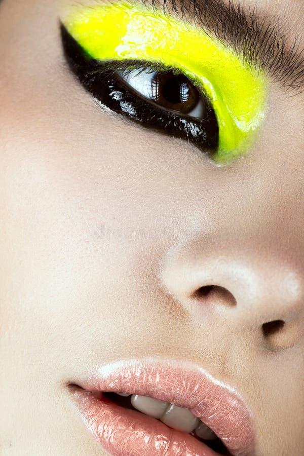 Närbildstående av flickan med idérik konst för guling- och svartsmink Härlig le flicka arkivbild