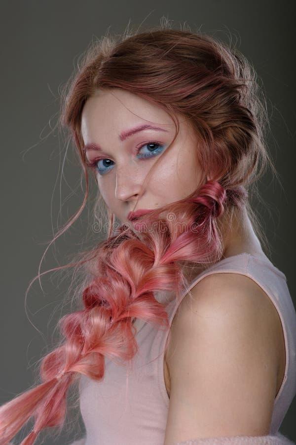 Närbildstående av flickan med rosa hår i flätad tråd-, rosa färg- och blåttmakeup Flickaanseende på en mörk bakgrund som täckas h royaltyfri bild