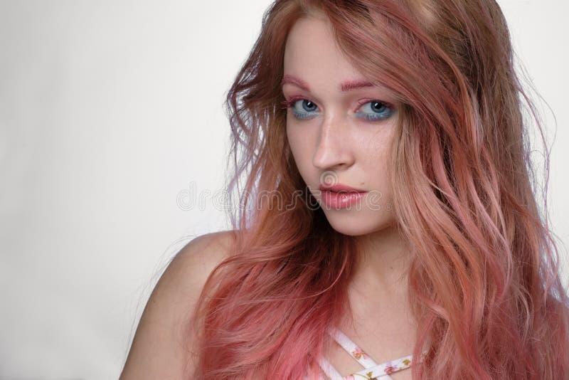 Närbildstående av flickan med rosa hår- och rosa färg-och-blått smink på ljus bakgrund royaltyfria foton