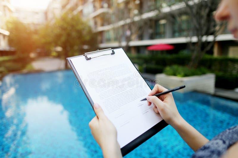 Närbildstående av flickan som undertecknar dokument på bakgrund av pölen för den soliga dagen Framdel som används med den öppna s royaltyfri foto