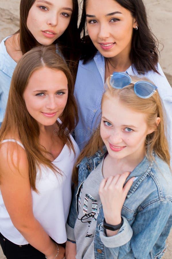 Närbildstående av fyra unga härliga flickvänner i sommar på stranden fotografering för bildbyråer