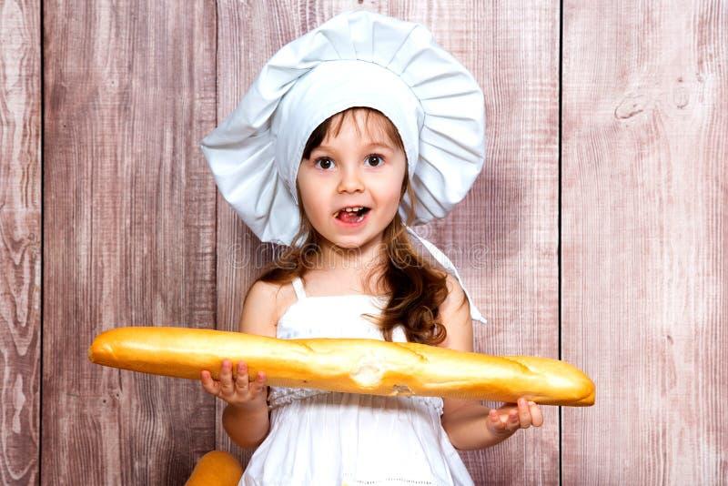 Närbildstående av lite att le flickan i ett laga mat lock med en ny bagett i hennes händer royaltyfri fotografi