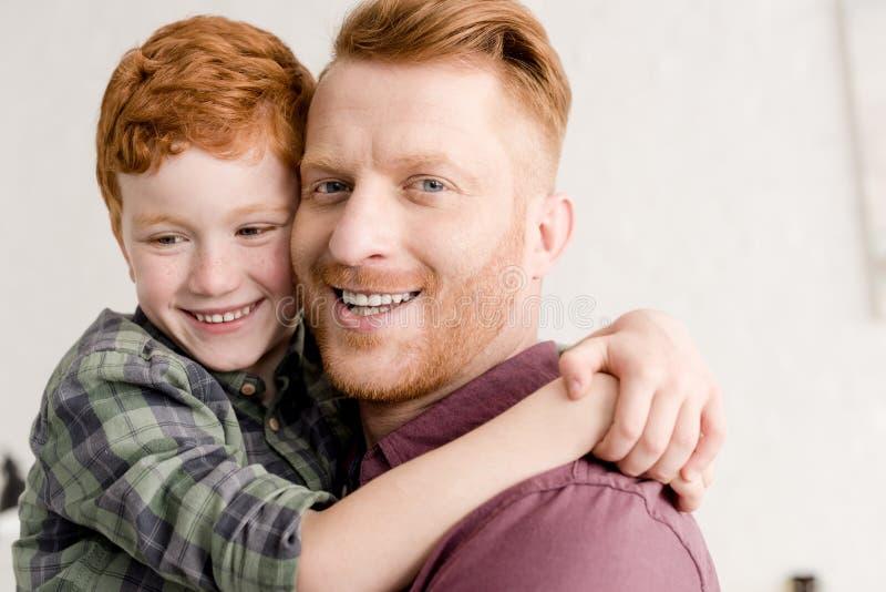 närbildstående av lyckligt krama för för rödhårig manfader och son royaltyfri bild