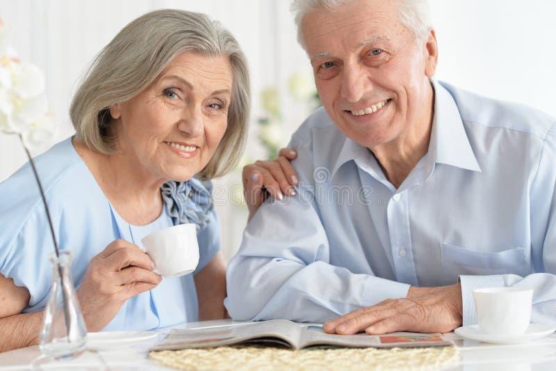 Närbildstående av mogna par med tidskriften som dricker te fotografering för bildbyråer