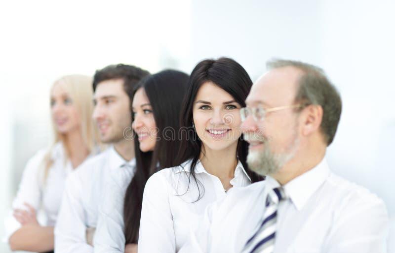 Närbildstående av utövande affärsfolk som i rad står på kontoret och ser kameran royaltyfri bild