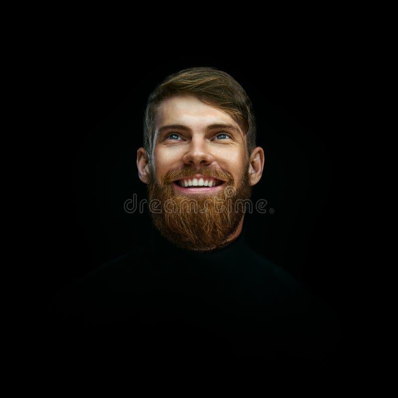 Närbildståenden av att skratta den unga skäggiga mannen weared svart tur royaltyfri fotografi