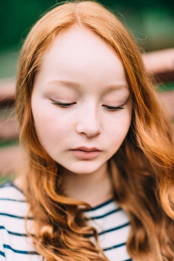 Närbildståenden av den älskvärda fundersamma flickan med långt lockigt rött hår i sommar parkerar Utomhus- stående av en rödhårig arkivfoton