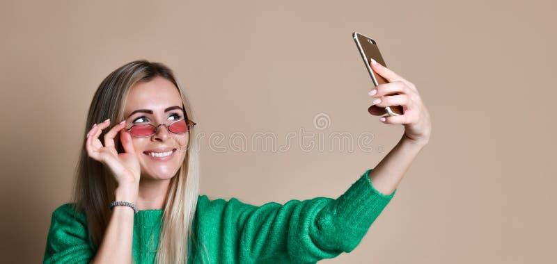 Närbildståenden av den blonda kvinnan för ungt gladlynt mode i tröjakläder gör selfie på smartphonen, över beige bakgrund arkivbilder