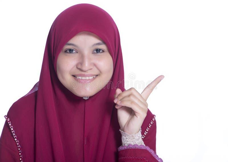 Närbildståenden av den härliga muslimska flickan pekar hennes finger Över vitbakgrund royaltyfri fotografi
