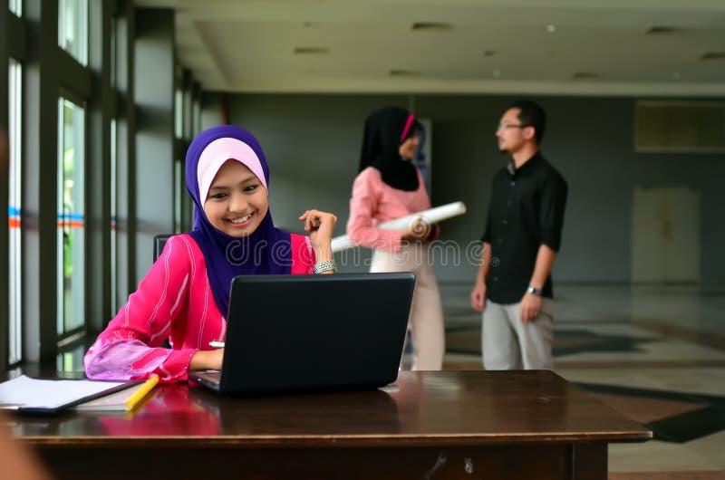 Närbildståenden av den härliga unga asiatiska studenten studerar tillsammans arkivfoto