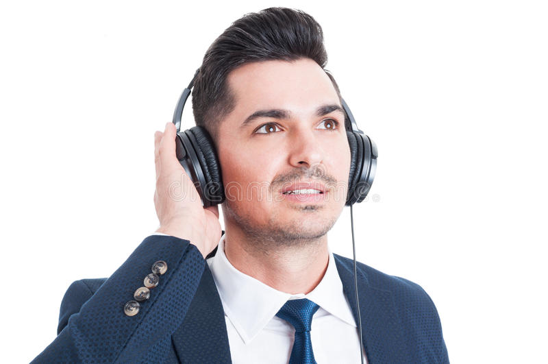 Närbildståenden av den stiliga affärsmannen med hörlurar lyssnar arkivbild