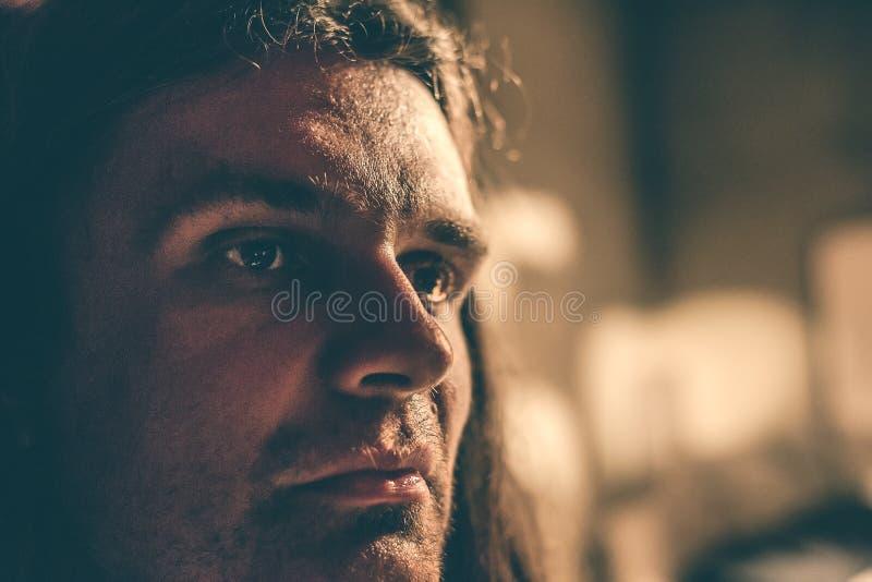 Närbildståenden av en allvarlig ung manlig hipster med långt hår, man ser allvarligt royaltyfria foton