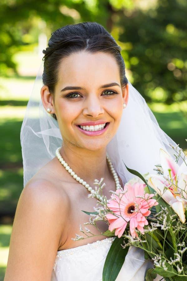 Närbildståenden av en härlig brud med buketten parkerar in royaltyfri bild