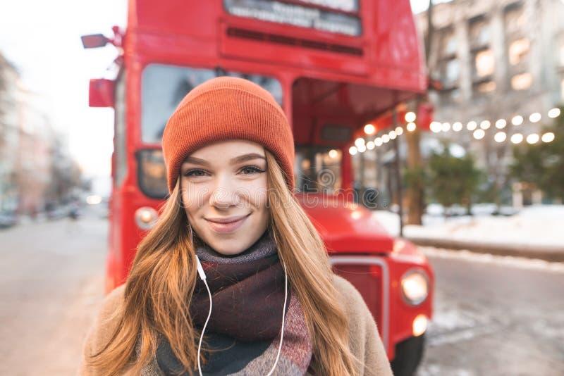 Närbildståenden av en positiv flicka i hörlurar ser kameran på baksidan av en röd buss Gullig le flicka i hörlurar arkivbild