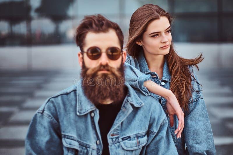 Närbildståenden av ett hipsterpar av en brutal skäggig man i solglasögon och hans iklädda jeans för flickvän klår upp royaltyfria foton