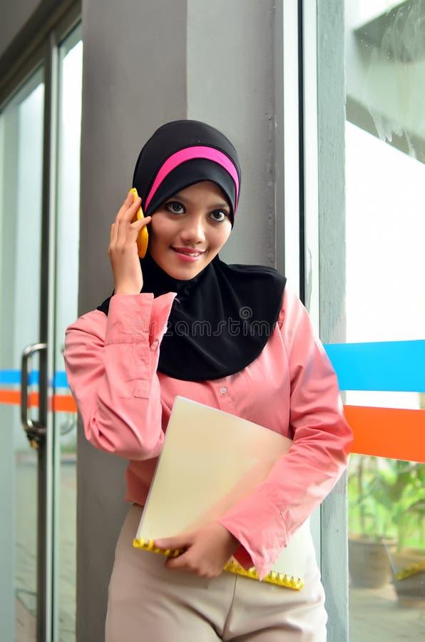 Närbildståenden av härliga unga asiatiska affärskvinnor ler med mobiltelefonen arkivbild