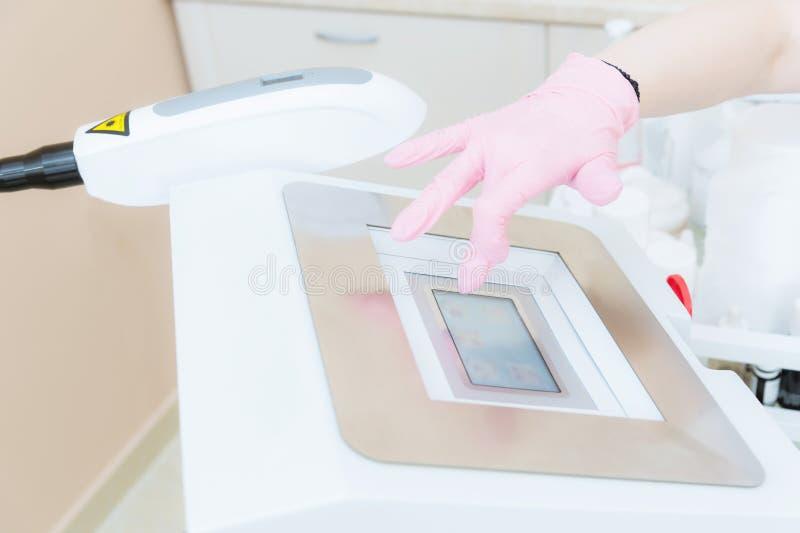 Närbildung flickakosmetologen inkluderar en apparat för kollokalvård på pekskärmen i kontoret av cosmetology royaltyfri foto