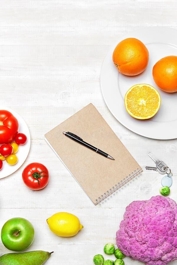 näring bantar Nya grönsaker och anteckningsbok på tabellen arkivbilder