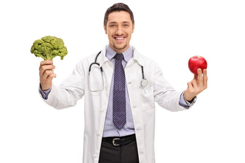 Näringsfysiolog rymma broccoli och ett äpple royaltyfri fotografi