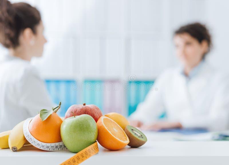 Näringsfysiolog som möter en patient i kontoret royaltyfri foto