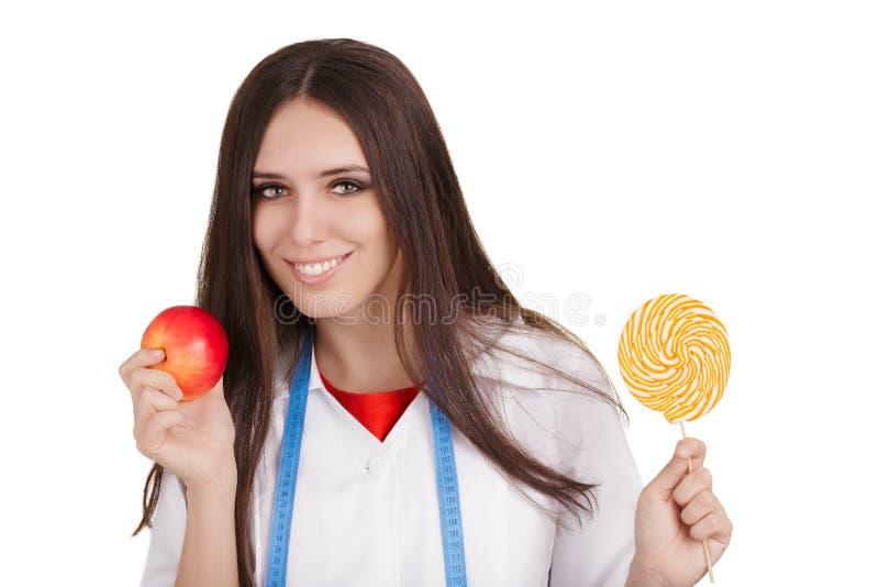 Näringsfysiolog som rymmer en Apple och en stor godis fotografering för bildbyråer